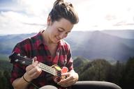 Happy woman playing ukelele against mountain range - CAVF34007