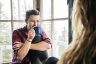 Woman enjoying coffee in cottage - CAVF34016