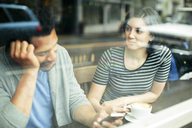 Woman looking at man using smart phone while sitting in cafe seen through glass window - CAVF34037