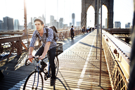 Man riding bicycle on Brooklyn Bridge against clear sky - CAVF34064