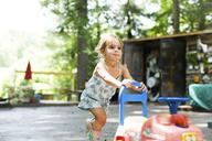 Cute girl pushing toy car in backyard - CAVF34169