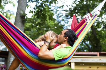 Man kissing daughter on forehead while relaxing in hammock at backyard - CAVF34175