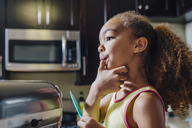 Cute girl licking thumb while baking in kitchen - CAVF34202