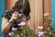 Woman photographing flowers through camera - CAVF34242