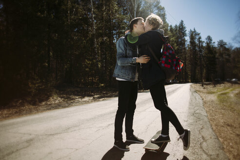 Romantic couple kissing while standing on road in forest during sunny day - CAVF34263