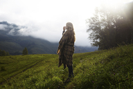 Full length of woman wrapped in blanket standing on grassy field during foggy weather - CAVF34284