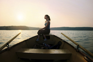 Thoughtful woman sitting on ship's bow at canoe against clear sky during dusk - CAVF34299