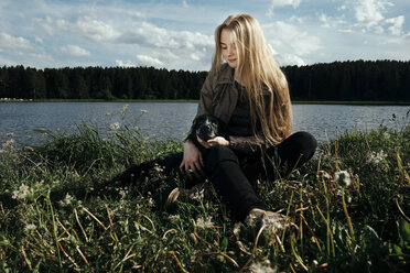 Woman sitting with dog by lake against cloudy sky - CAVF34302