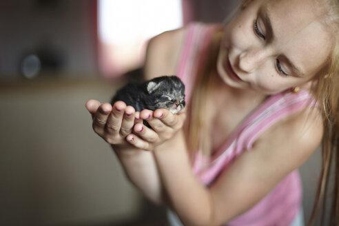 Girl holding kitten at home - CAVF34305