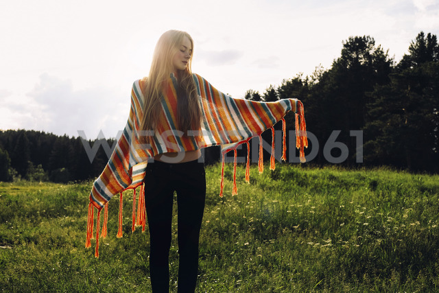 Relaxed woman wearing poncho while standing on grassy field - CAVF34311 - Cavan Images/Westend61