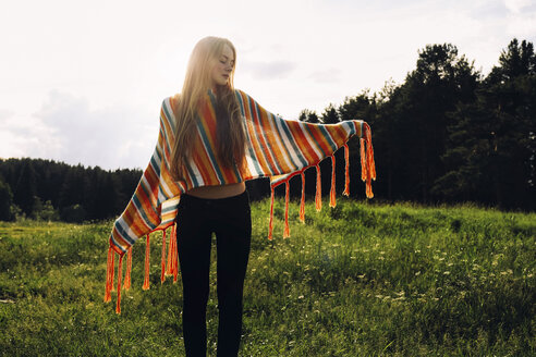 Relaxed woman wearing poncho while standing on grassy field - CAVF34311