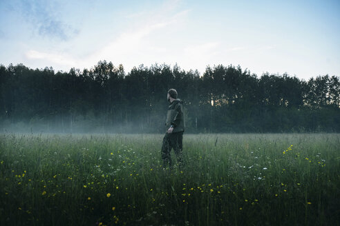 Side view of man standing on grassy field against sky during foggy weather - CAVF34320