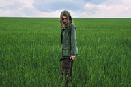 Woman standing on grassy field against cloudy sky - CAVF34335