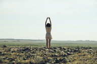 Rear view of woman stretching while standing on rocky field against clear sky - CAVF34347