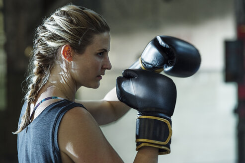 Side view of confident female boxer in gym - CAVF34437