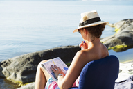 Woman sitting in chair and reading newspaper on rocky beach - FOLF09222