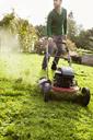Man mowing domestic garden lawn - FOLF09306
