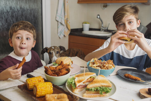 Two boys with dog enjoying american food at dining table at home - SKCF00394