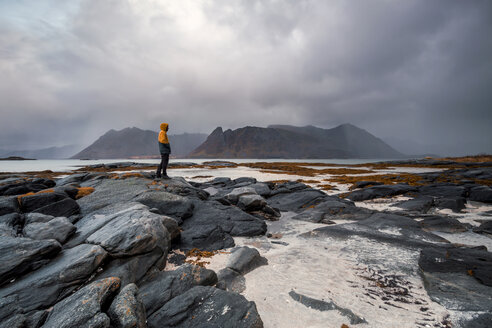 Norway, Lofoten Islands, Gimsoysand, man standing at rocky coast - WVF00928