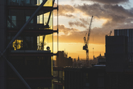 UK, London, buildings and crane silhouette at sunset with Big Ben and Westminster in far background - WPEF00154