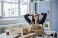 Portrait of young architect looking at architectural model in office - GUSF00600