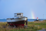 Norway, Lofoten Islands, Eggum, ship at the coast and rainbow above the sea - WVF00935
