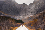 Norway, Lofoten Islands, man standing on empty road surrounded by rock face - WVF00944