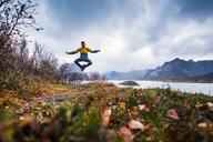 Norway, Lofoten Islands, man jumping at the coast - WVF00959