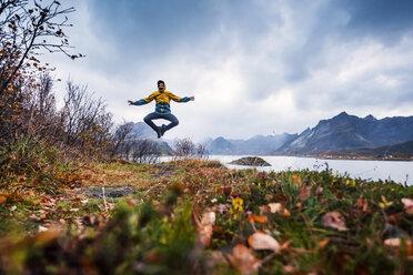 Norway, Lofoten Islands, man jumping at the coast - WVF00959