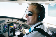 Confident smiling pilot wearing ear muff sitting in cockpit - MASF00008