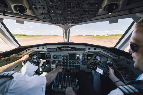 Pilots using control panel in cockpit - MASF00011