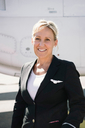 Portrait of confident smiling air stewardess standing against airplane - MASF00014