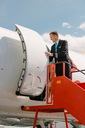 Pilot standing on staircase entering in airplane against sky - MASF00020