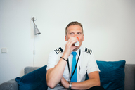 Pilot drinking coffee while sitting on sofa against wall at airport - MASF00026