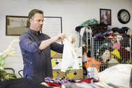 Mature male volunteer examining fabric at warehouse - MASF00035