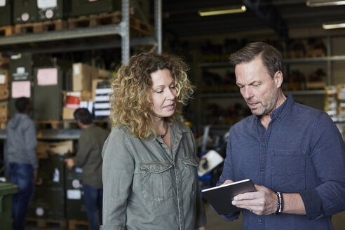 Mature colleagues discussing over digital tablet at warehouse - MASF00053