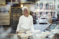 Portrait of senior smiling baker at bakery seen from glass window - MASF00074