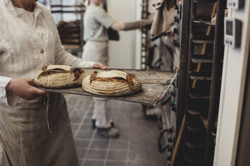 Midsection of baker keeping fresh baked breads on cooling rack at bakery - MASF00077