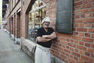 Portrait of senior male baker leaning on brick wall outside bakery - MASF00086