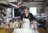 Portrait of senior male owner standing with fabric at workbench in workshop - MASF00110