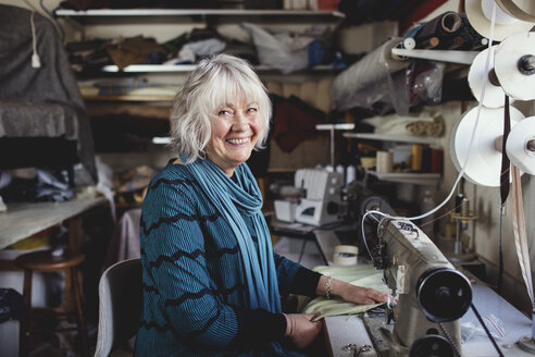 Portrait of smiling senior owner sitting at sewing machine in workshop - MASF00116
