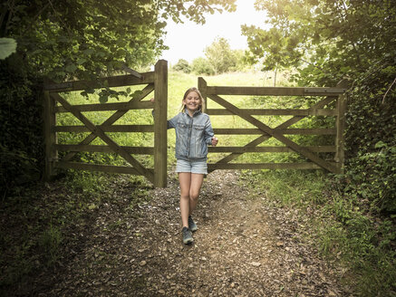 Full length of smiling girl standing by wooden gate on footpath amidst plants - MASF00128