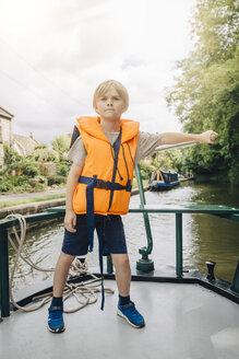 Full length of confident boy steering boat in river against sky - MASF00131