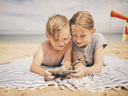 Smiling siblings sharing smart phone while lying on towel at beach against sky - MASF00137