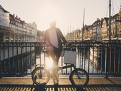 Full length back lit of man standing with bicycle and shopping bags on footbridge in city - MASF00140