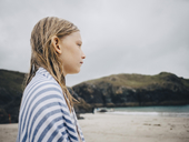 Side view of blond girl wrapped in striped blue towel standing at beach against sky - MASF00143