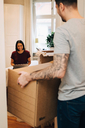 Man carrying box towards woman sitting in bedroom - MASF00149
