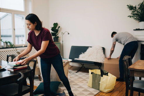 Woman arranging books on table while unpacking boxes in living room at new home - MASF00152