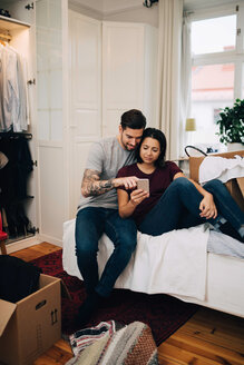 Couple using mobile phone while resting on bed in bedroom - MASF00158