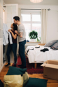 Man and woman arranging clothes together in closet at new home - MASF00164